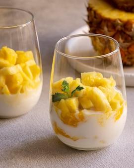 ガラスにヨーグルトとパイナップルを入れた健康的な食事