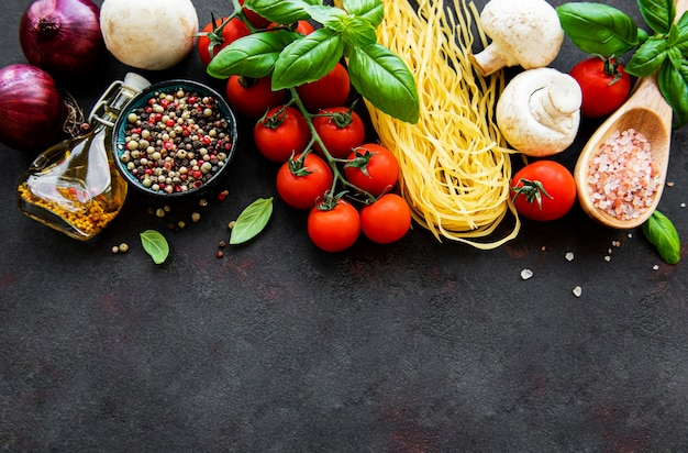 Healthy mediterranean diet with spaghetti, tomatoes, basil, olive oil, garlic, peppers on black surface