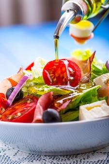 Здоровый средиземноморский салат с оливками, помидорами, пармезаном и ветчиной прошутто, залив оливковым маслом