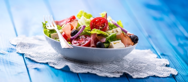 Здоровый средиземноморский салат с оливками, помидорами, пармезаном и ветчиной прошутто