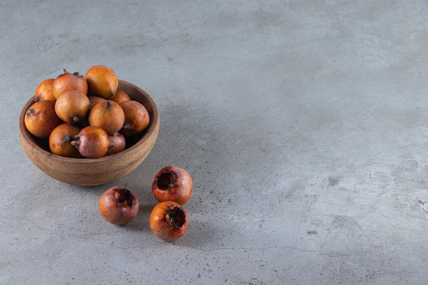 Здоровые плоды мушмулы в белой миске на каменном фоне.