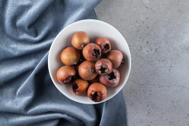 돌 배경에 놓인 하얀 그릇에 건강한 메들라 과일.
