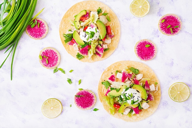 Healthy mexican corn tacos with boiled chicken breast, avocado and watermelon radish and yogurt dressing.