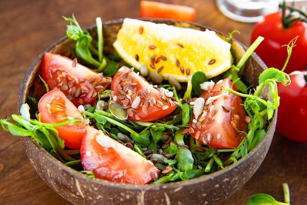 토마토와 씨앗 클로즈업으로 건강 한 microgreen 샐러드. 고품질 사진