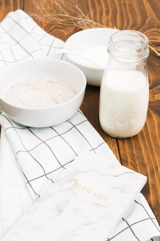 Healthy milk bottle; flour bowl and to do list over wooden panel