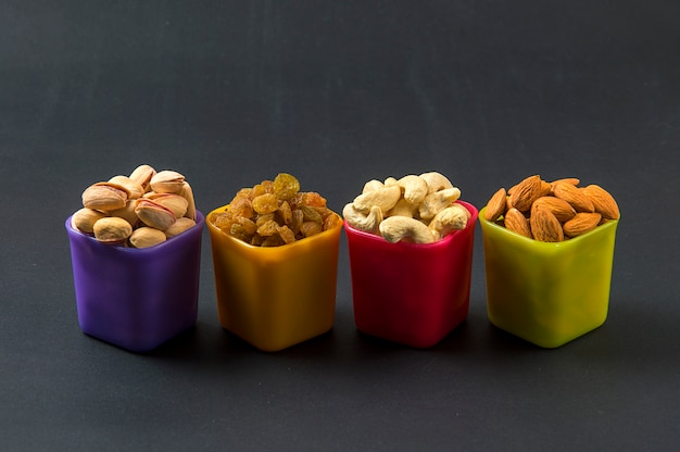 Healthy mix dry fruits and nuts on dark background. almonds, pistachio, cashews, raisins