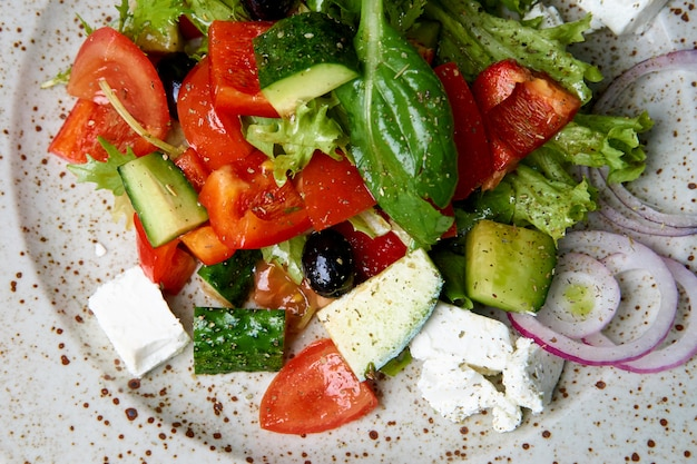 Healthy mixed salad with greens, cucumber, onion, tomatoes and feta cheese.