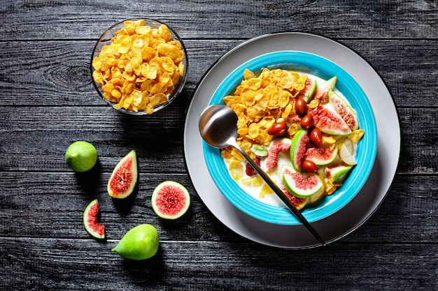 Healthy morning breakfast: blue bowl with natural plain yogurt with crispy corn flakes, figs, pear served on a black wooden surface, top view, close-up