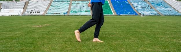 Здоровый утренний бег, спортсмен-мужчина на поле с зеленой травой босиком