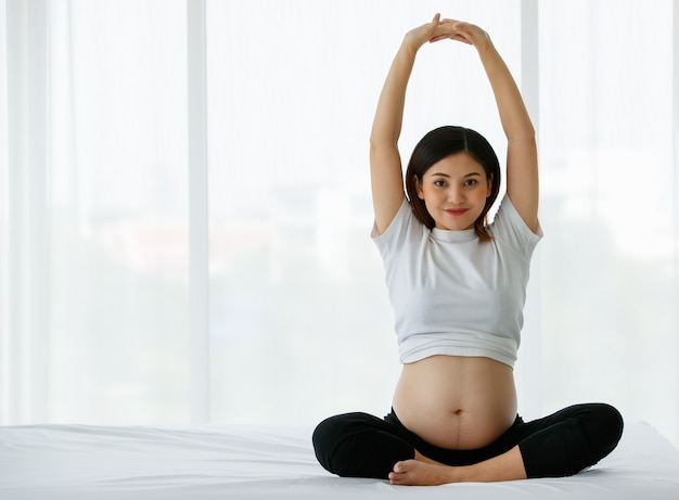 Healthy mother concept. young beautiful pregnant woman wearing a white t-shirt and black pants sitting on a bed raises her hands above her head doing stretching after yoga exercise.