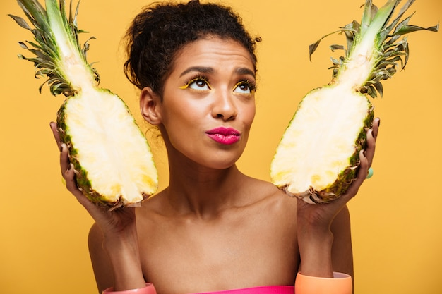 Healthy mulatto woman with colorful makeup looking upward and holding fresh ripe pineapple split in half isolated, over yellow wall