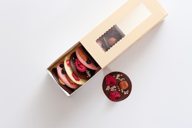 Healthy multicolored handmade chocolate on a beige box on white background