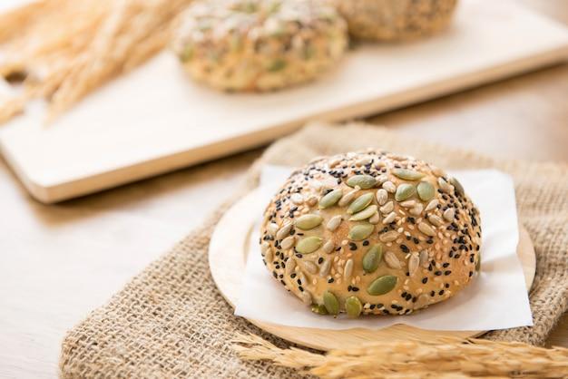 A healthy multigrain bread bun on a wooden plate in a bakery