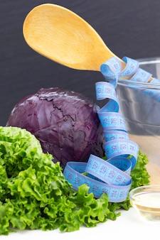 紫キャベツとレタスのヘルシーなナチュラルフレッシュサラダ。ダイエット、菜食主義。テーブルの上の巻尺。縦の写真