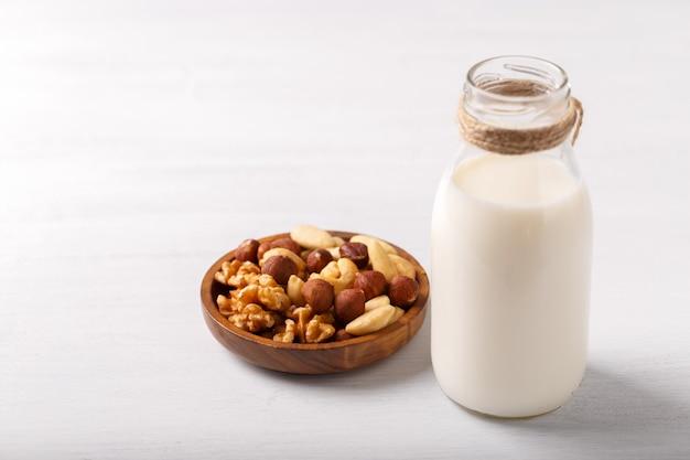 유리에 든 건강한 천연 비 유제품 우유와 흰색 나무 테이블에 견과류 한 그릇