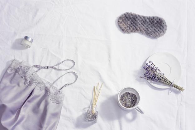 Концепция здорового ночного сна, шелковая пижама, маска для сна, чашка чая с лавандой, ароматы для лучшего засыпания, мягкая подушка на белом постельном белье, плоская укладка.