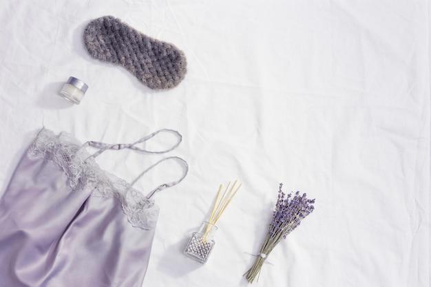 Концепция здорового ночного сна, шелковая пижама, маска для сна, чашка лавандового чая, ароматы для лучшего засыпания, мягкая подушка