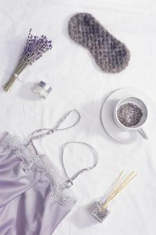 健康的な夜の睡眠のコンセプト、シルクのパジャマ、睡眠マスク、ラベンダーティーのカップ、より良い眠りのためのアロマ