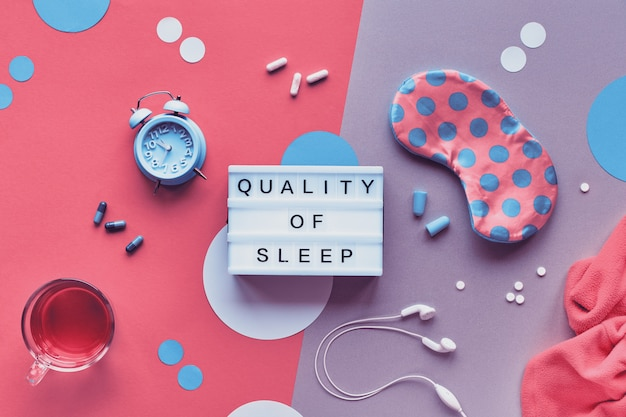 Healthy night sleep creative concept. sleep mask, alarm clock, earphones, earplugs, pills and sleep supplement. split two tone coral and purple paper with abstract circles and palm leaves.