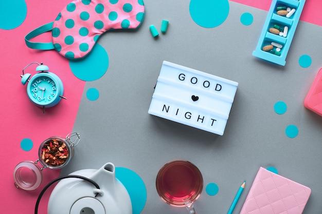 Healthy night sleep creative concept. sleep mask, alarm clock, earphones, earplugs and pills. split two tone, with circles and tea. lightboard with text
