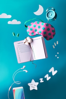 Healthy night sleep creative concept with sleep log handwritten diary. flying or levitating sleeping mask, alarm clock, earphones, earplugs, pills.