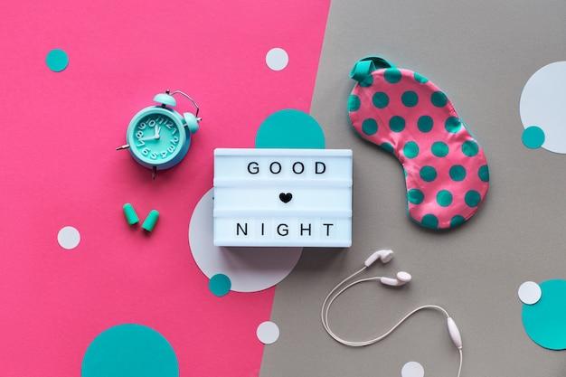 Healthy night sleep creative flat lay. sleeping mask, alarm clock, earphones, earplugs, tea and pills. split pink craft paper background with light garland. light box, text