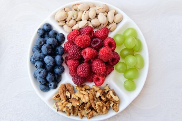 Здоровое питание, ягоды и орехи. земляника, виноград, черника, грецкие орехи, фисташки. эко питание концепция смешанные ягоды и орехи. dslr роялти свободный образ, здоровый завтрак