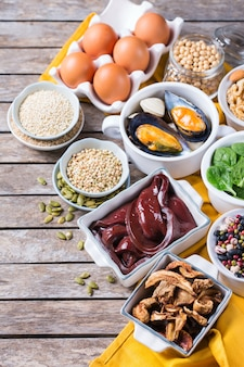 Healthy nutrition dieting concept. assortment of foods high in iron. beef liver, spinach, eggs, legumes, nuts, mushrooms, quinoa, sesame, pumpkin seeds, soy beans, seafood. copy space, flat lay