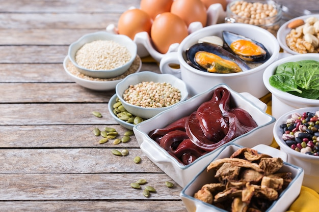 Healthy nutrition dieting concept. assortment of foods high in iron. beef liver, spinach, eggs, legumes, nuts, mushrooms, quinoa, sesame, pumpkin seeds, soy beans, seafood. copy space