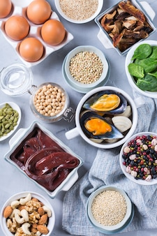 Healthy nutrition dieting concept. assortment of foods high in iron. beef liver, spinach, eggs, legumes, nuts, mushrooms, quinoa, sesame, pumpkin seeds, soy beans, seafood. flat lay