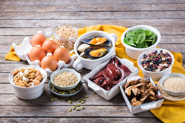 Healthy nutrition dieting concept. assortment of foods high in iron. beef liver, spinach, eggs, legumes, nuts, mushrooms, quinoa, sesame, pumpkin seeds, soy beans, seafood.