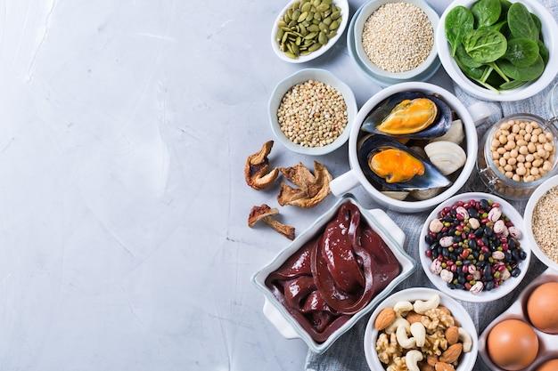 Концепция здорового питания диеты. ассортимент продуктов с высоким содержанием железа. говяжья печень, шпинат, яйца, бобовые, орехи, грибы, киноа, кунжут, тыквенные семечки, соевые бобы, морепродукты. копирование пространства, плоская планировка