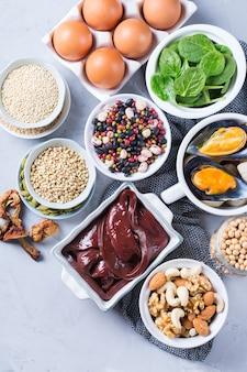 Концепция здорового питания диеты. ассортимент продуктов с высоким содержанием железа. говяжья печень, шпинат, яйца, бобовые, орехи, грибы, киноа, кунжут, тыквенные семечки, соевые бобы, морепродукты. плоская планировка