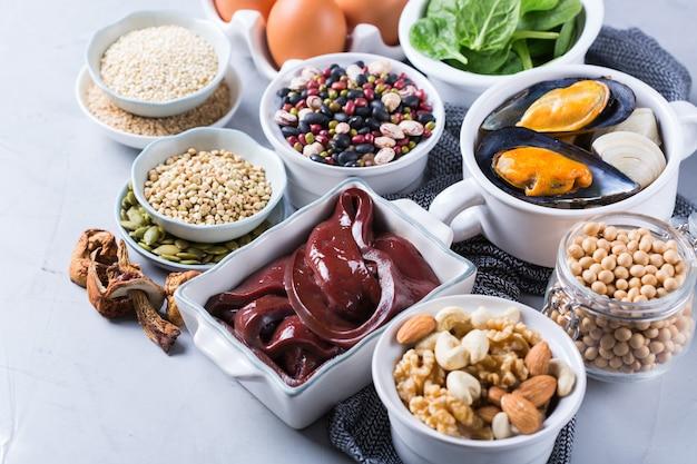 Концепция здорового питания диеты. ассортимент продуктов с высоким содержанием железа. говяжья печень, шпинат, яйца, бобовые, орехи, грибы, киноа, кунжут, тыквенные семечки, соевые бобы, морепродукты.