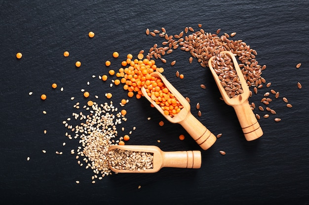 Healthy nutrition food flax, sesame and orange lentil seeds in bamboo scoop with copy space