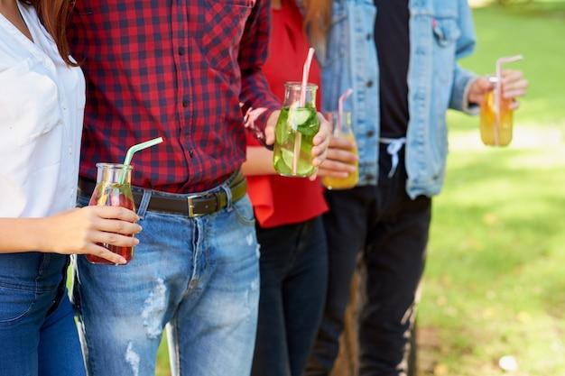 건강한 영양. 녹색 자연 배경에 신선한 주스 해독을 마시는 친구. 청소년 라이프 스타일, 채식주의 식단, 피트니스 음식, 성공적인 체중 감량 개념