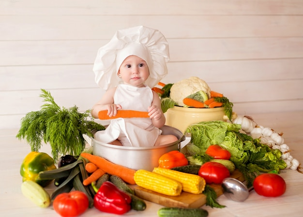 Healthy nutrition happy little girl in an apron and hat prepares a vegetable salad. cook