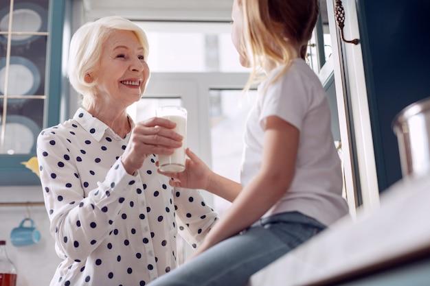 건강한 영양. 그녀의 작은 손녀에게 우유 한 잔을 나눠주고 소녀가 부엌 카운터에 앉아있는 동안 그녀에게 다정하게 웃고있는 즐거운 노인 여성