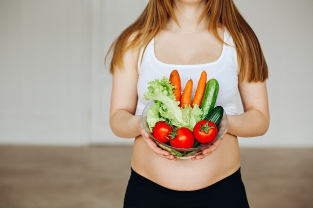 Healthy nutrition and pregnancy. close-up pregnant woman's belly and vegetable salad.