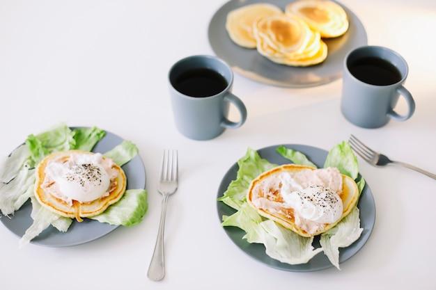 Здоровый питательный вкусный завтрак с блинами, яйцом-пашот на керамической тарелке и кофейной чашке