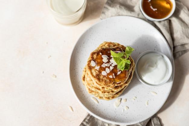 Полезные овсяные оладьи с джемом и мятой на керамической тарелке веганский завтрак