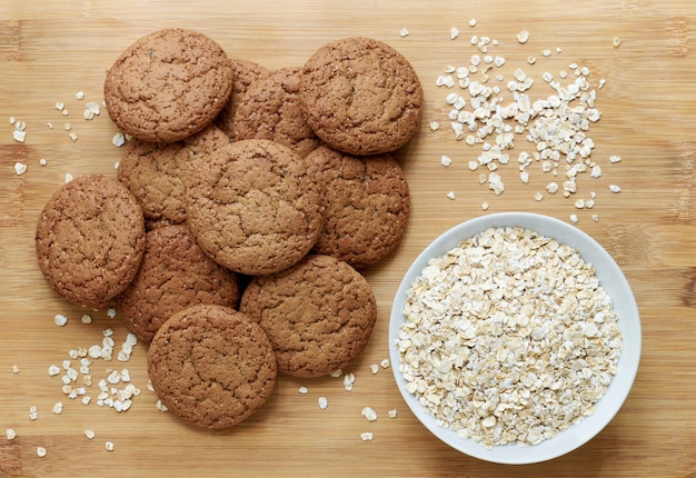 Healthy oatmeal cookies and oat flakes in bowl on wooden table, top view
