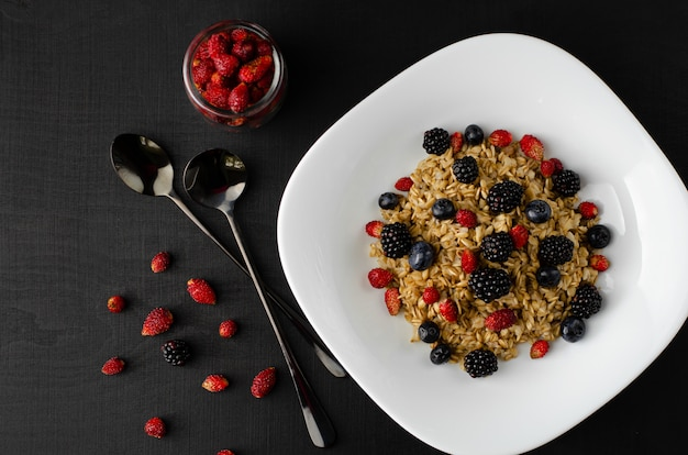 Healthy oatmeal porridge with mix of wild berries on dark background