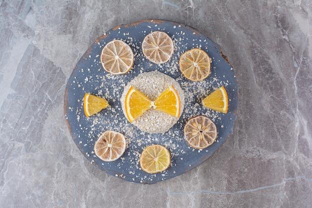 Здоровая овсяная каша с кусочками апельсина на деревянном куске.