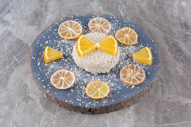 Healthy oatmeal porridge with slices of orange fruit on a wooden piece.