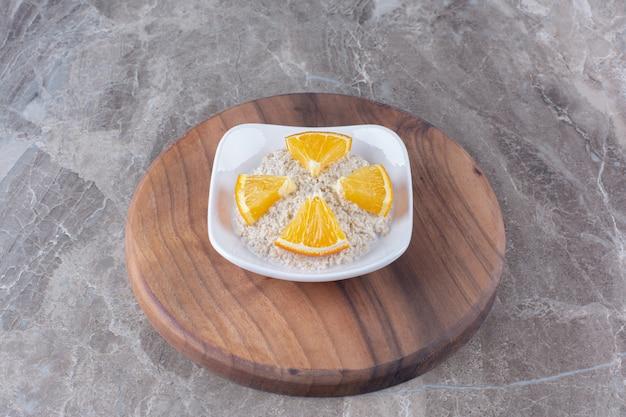 Healthy oatmeal porridge with slices of orange fruit on wooden piece.
