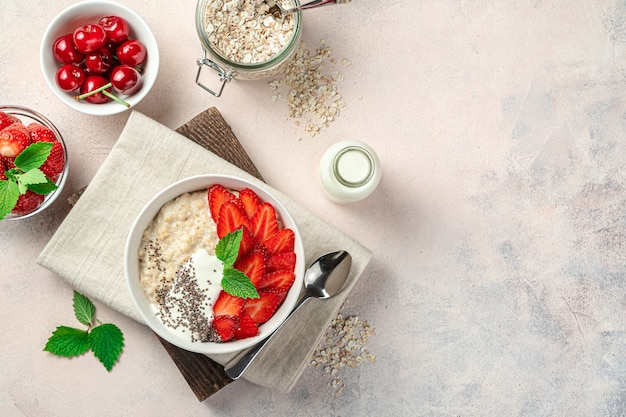 Healthy oatmeal porridge with strawberries, cherries, yogurt and chia seeds on a pink background with space to copy. healthy food.