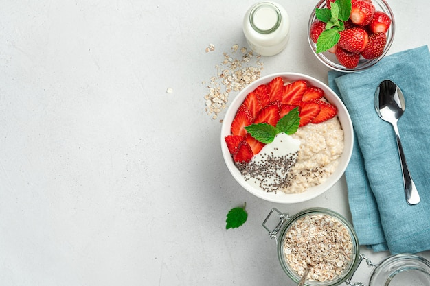 Healthy oatmeal porridge with strawberries chia seeds and yogurt on a gray background with space to ...