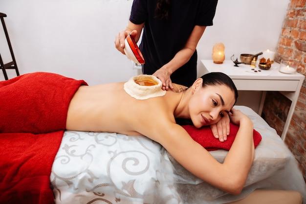 건강한 기름. 살롱에서 아유르베 다 치료를받는 동안 그녀의 등에 의료 오일을 느끼는 쾌적한 차분한 고객