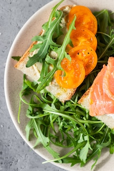 Healthy open sandwiches with artisan bread with cream cheese, salmon, tomatoes and arugula